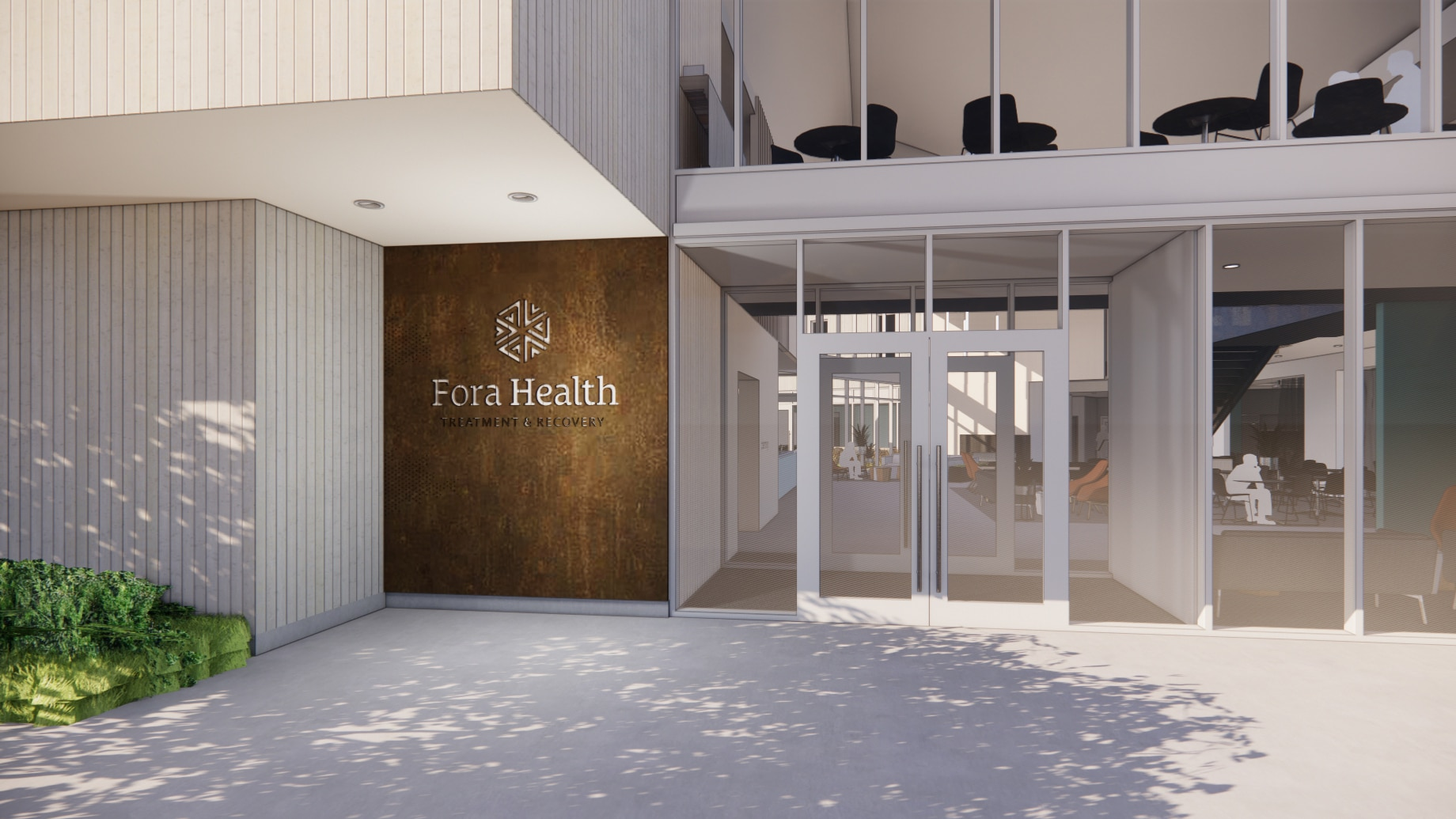 View of entrance to Fora Health. Glass doors and rusted metal wall with logo