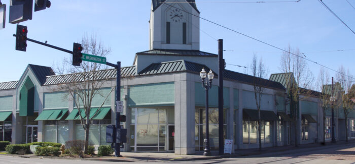 Exterior of gray and teal building with clock on spire